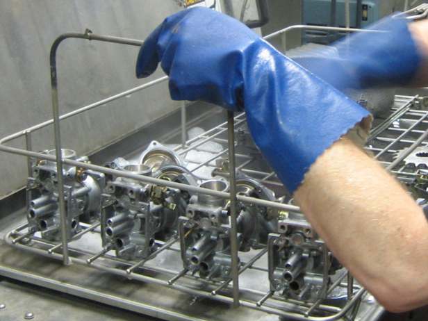 Ultrasonically cleaning carburetors as part of rebuilding
